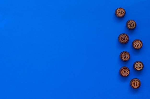 Barils de loto en bois sur une surface bleue. cocept avec des nombres