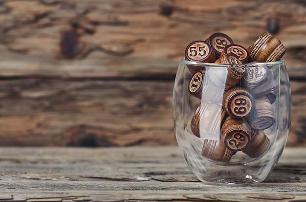 Barils avec des nombres dans une tasse en verre sur un fond en bois