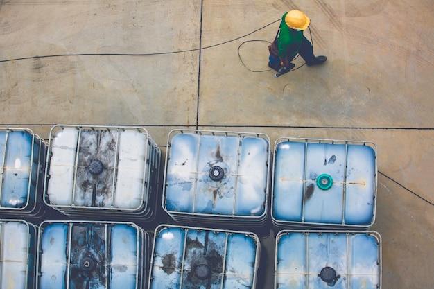 Barils de pétrole blanc ou mâle marchant des tambours chimiques empilés
