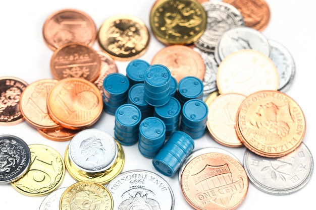 Barils de pétrole bleu et pièces sur fond blanc