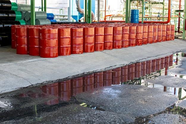Barils de pétrole fûts rouges ou chimiques empilés verticalement réflexe eau industrielle