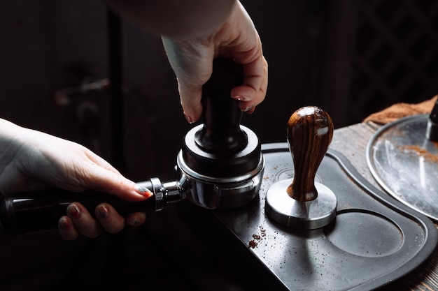 Barista en appuyant sur le café moulu dans le porte-filtre avec un tamper.