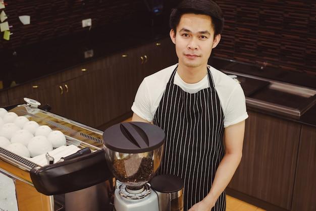 Barista asiatique beau jeune homme faisant du café avec une machine à café au comptoir café.