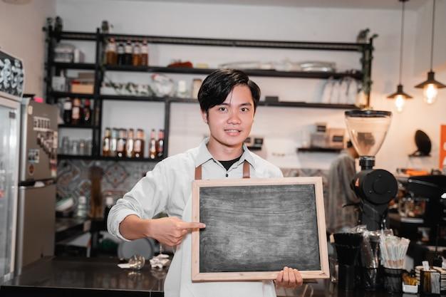 Barista asiatique tenant et pointant une planche en se tenant devant le pub
