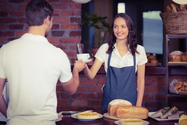 Barista assez souriant desservant un client