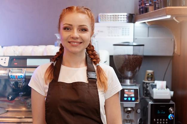Barista aux cheveux rouges posant dans un café