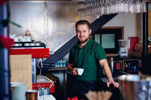 Barista barman avec café à la main derrière le bar