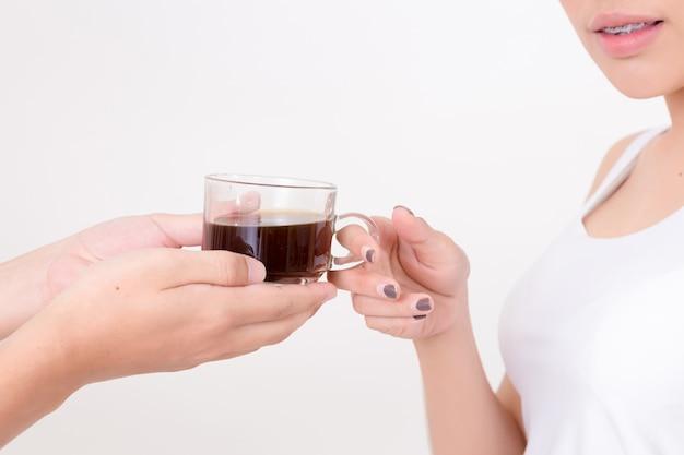 Barista donnant une tasse de café à une jeune femme asiatique.