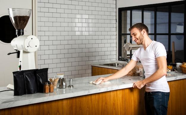 Barista essuyant le comptoir avec le chiffon