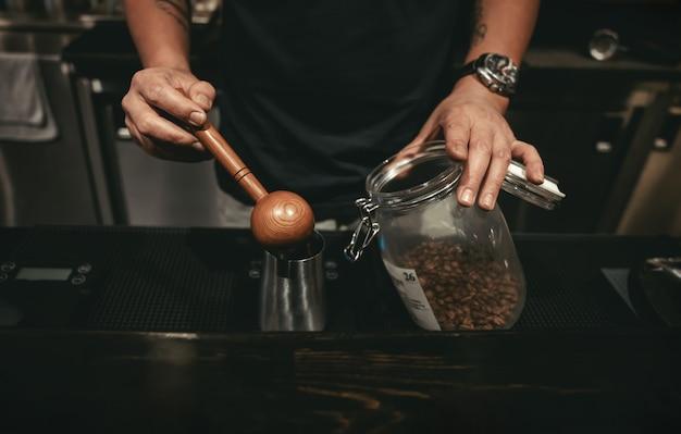 Un barista faisant du café dans le café. en utilisant une cuillère en bois pour mesurer les grains de café