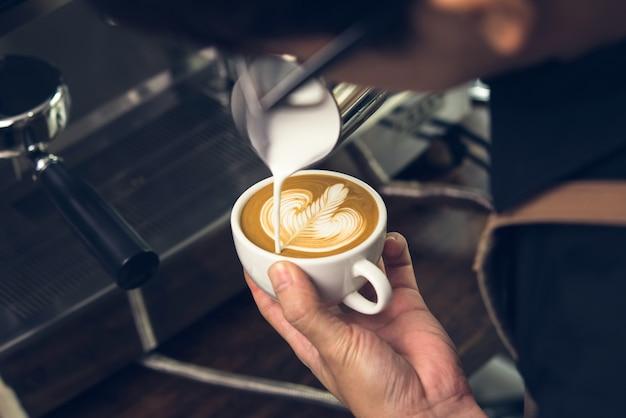 Barista faisant la forme de rosetta café d'art latte