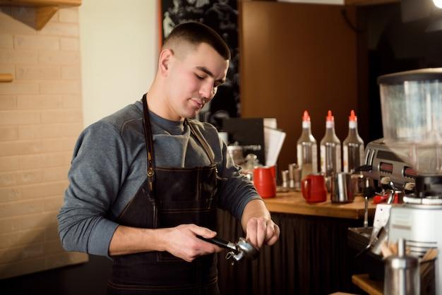 Un barista fait un café au bar.