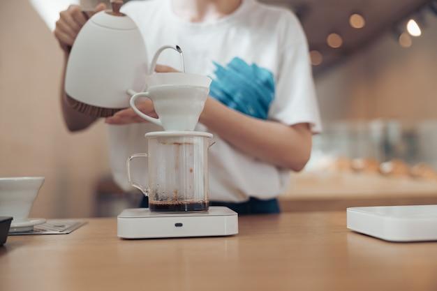Barista femme faisant du café filtre à la cafétéria