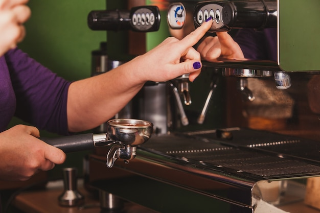 Barista en gros plan moulant du café pour un expresso aromatisé