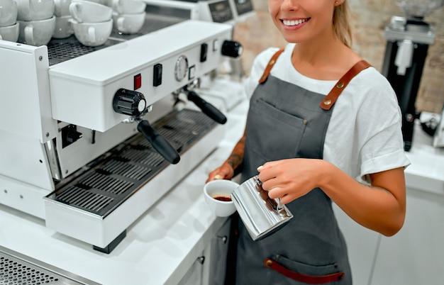 Le barista de la jeune femme séduisante prépare le café dans un café.