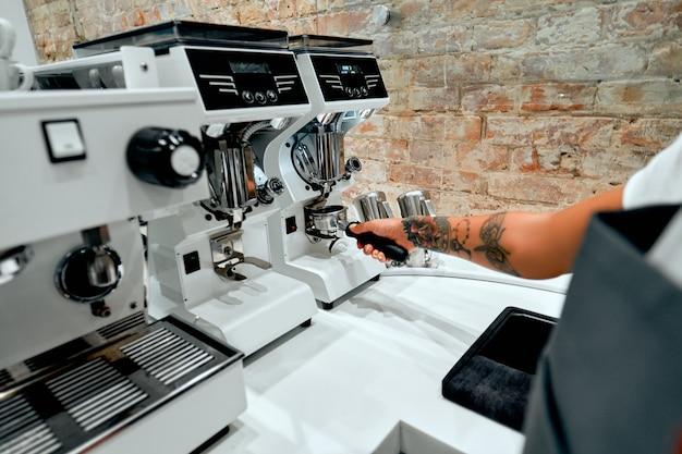 Le barista d'une jeune femme séduisante prépare du café pour le client sur une machine à expresso dans un café.