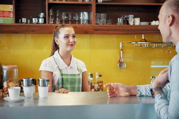 Barista parlant et gestionnaire dans un café
