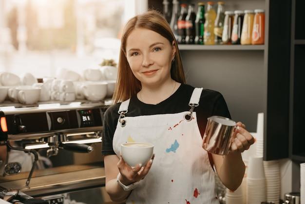 Un barista posant avec une tasse de lait en métal et une tasse de latte près d'une machine à expresso