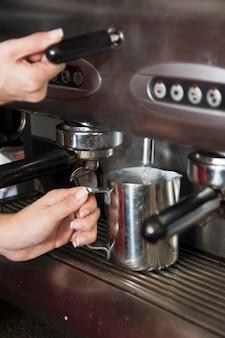 Barista prend l'eau chaude du robinet dans la tasse