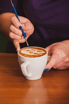 Barista préparant une tasse de café latte art avec un appareil métallique spécial - outil stylo latte-art