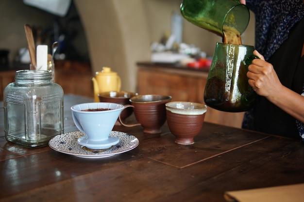 Barista prépare le café avec une cafetière et une bouilloire goutte à goutte. dégoulinant de café moulu avec filtre