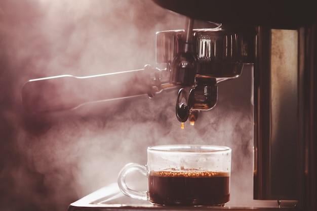 Barista prépare le café expresso en utilisant une machine à expresso haute pression dans un petit café.