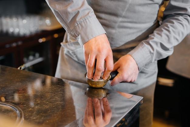 Le barista prépare un délicieux café dans un gros plan de café moderne.