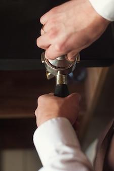 Barista presse le café moulu à l'aide d'un pilon.