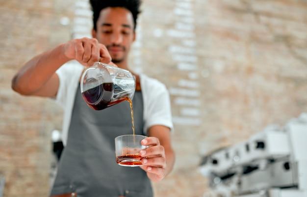 Un barista professionnel masculin africain séduisant en tablier prépare le café à la cafétéria.