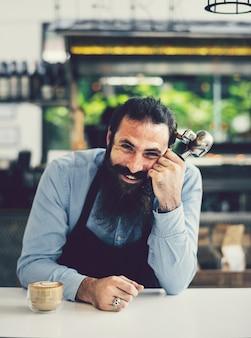 Barista souriant derrière le comptoir du café