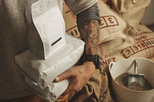 Barista tatoué détient des sacs d'emballage vierges avec des grains de café fraîchement cuits prêts pour la vente et la livraison