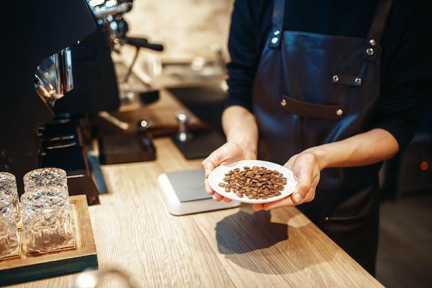 Barista tenant une assiette avec des grains de café frais