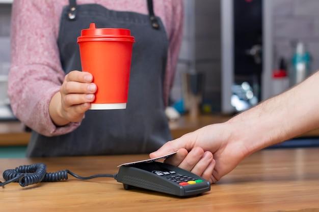 Barista tend un verre de papier rouge avec une boisson
