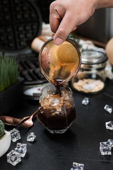 Barista versant du lait dans un verre de café glacé