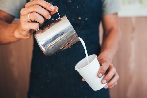 Le barista verse du lait d'une boîte de conserve dans du café dans un gobelet jetable en papier