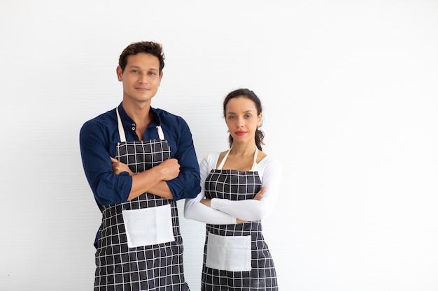 Baristas hispaniques homme et femme portant des bras de tablier noir croisés sur fond blanc.