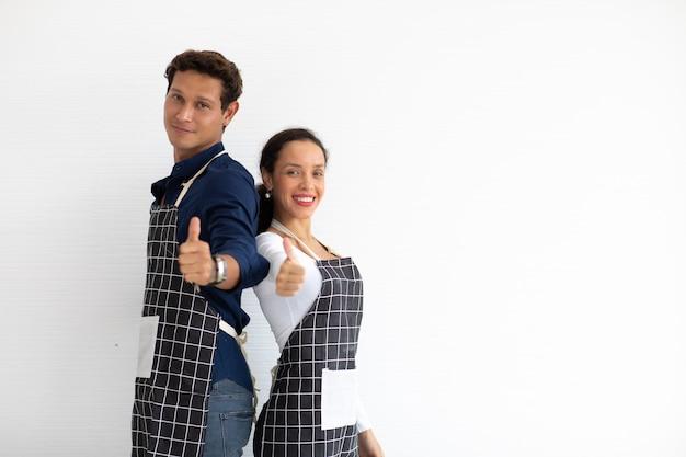 Baristas homme et femme hispaniques portant des pouces de tablier noir isolé sur fond blanc.