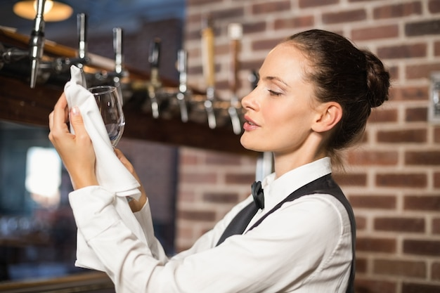 Barmaid nettoyant un verre