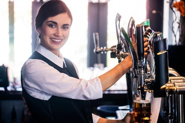 Barmaid servant une pinte dans un bar