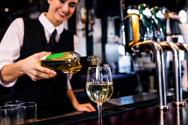 Barmaid servant un verre de vin dans un bar