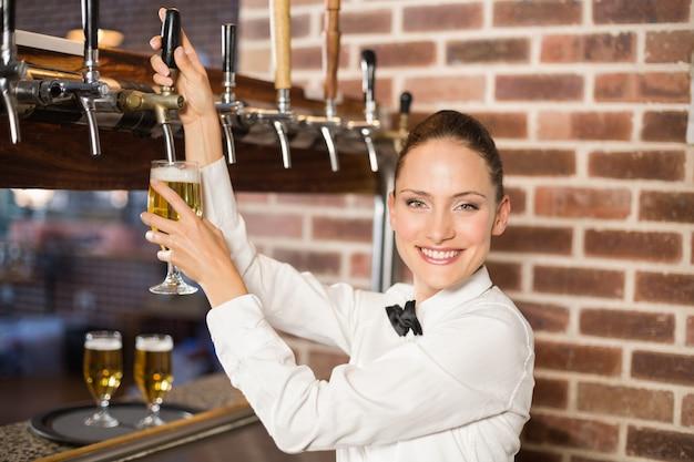Barmaid versant de la bière