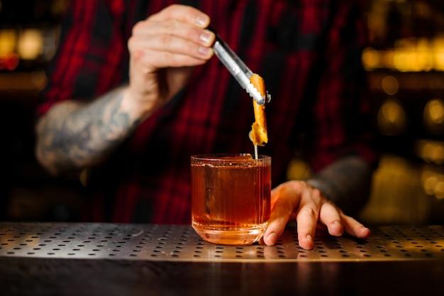Barman ajoutant à un cocktail à l'ancienne un zeste d'orange avec une pince à épiler sur le comptoir du bar