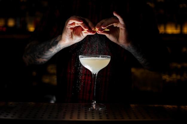 Barman ajoutant du jus de zeste d'orange à un cocktail courpse reviver dans le verre sur le comptoir du bar