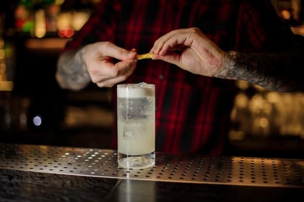Barman ajoutant du jus de zeste d'orange à un cocktail gin fizz dans le verre sur le comptoir du bar