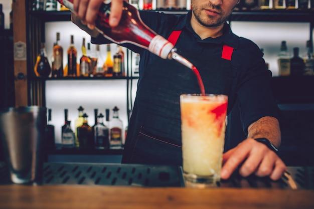 Barman ajoutant du sirop rouge dans le verre plein d'alcool blanc