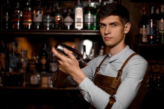 Barman attrayant tenant dans les mains un shaker en acier