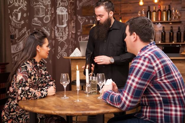 Barman barbu hipster montrant une bouteille de vin aux clients dans un pub ou un restaurant hipster vintage