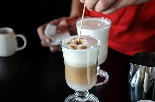 Le barman barista derrière le comptoir fait du café au lait, verse et empêche