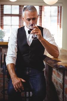 Barman, boire du vin au comptoir du bar