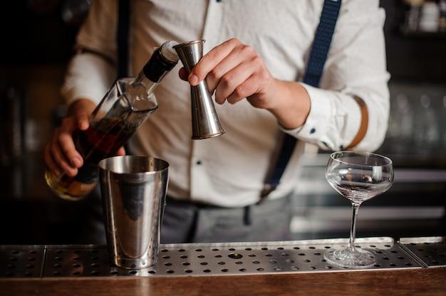 Barman en chemise fait cohabiller l'alcool sans visage